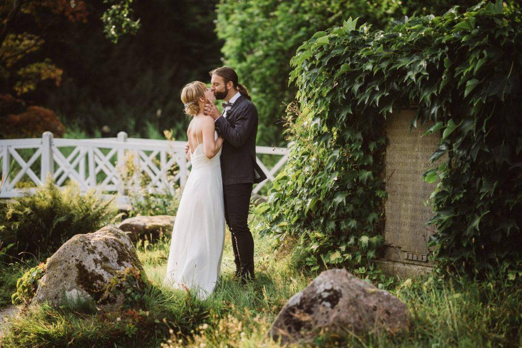 Hochzeitspaar küsst sich im Garten des Lütetsburger Schlosses