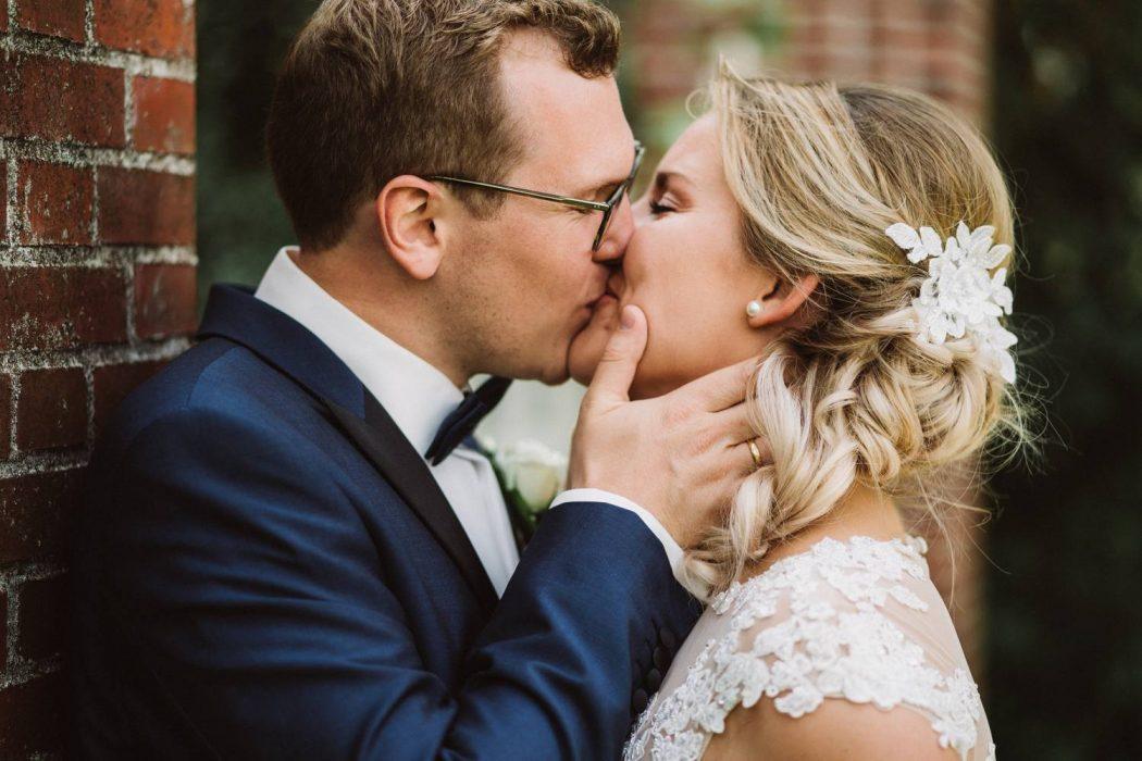 Junges Brautpaar küsst sich nach Ihrer Hochzeit im Bürgerpark Bremen